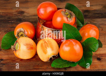 Kaki fruit on wood. Oriental East still life - Stock Photo