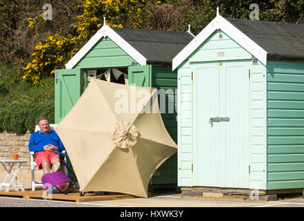Bournemouth - Man relaxing at beach huts at Bournemouth, Dorset UK  in March - Stock Photo