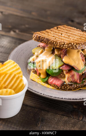 Big Homemade Sandwich with Roast Beef, Bacon, Pickles, Baby Spinach and Coleslaw Dressing in Toasted Bread - Stock Photo