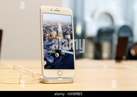 A brand new iPhone 7 Plus stands on display on a table in an Apple store. - Stock Photo