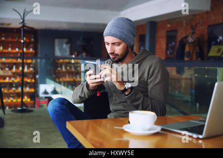 Young handsome hipster man with beard sitting in cafe talking mobile phone, holding cup of coffee and smiling. Laptop - Stock Photo