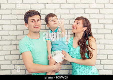 Happy and smiling young family Portrait on Brick wall Background. Father and Mother with Little Baby boy. Parents - Stock Photo