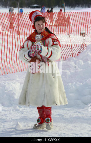 A dressed Sami woman observes while racers compete in reindeer race during St. Mary's Days festivities in Finnish - Stock Photo