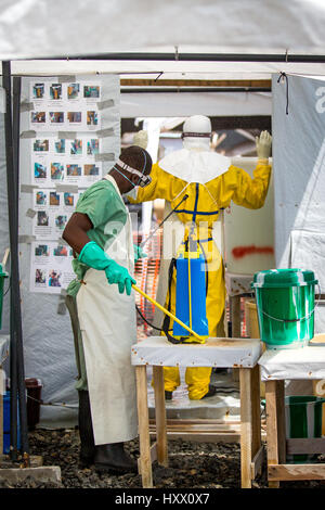 Sprayers at ELWA 1 disinfect healthcare workers entering and leaving this ETU in Monrovia set up by MSF. Everyone - Stock Photo