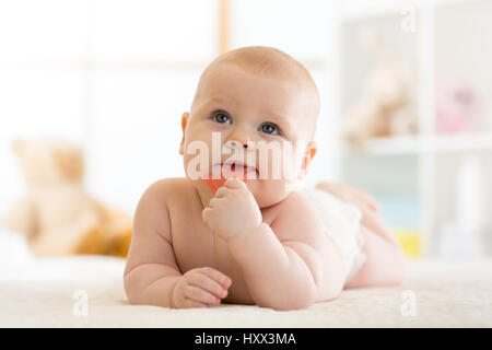 baby little child bites teether lying on bed weared diaper - Stock Photo