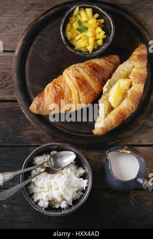 Breakfast with two croissant, butter, cottage cheese, cream and sliced mango fruit, served on wood round serving - Stock Photo