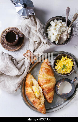 Breakfast with two croissant, butter, cup of coffee, cottage cheese and sliced mango fruit, served on serving metal - Stock Photo