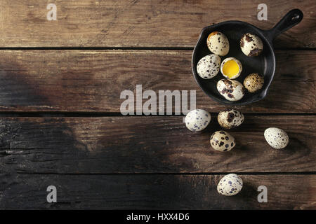 Whole and broken quail eggs with yolk in shell in small iron cast pan over old wooden plank background. Top view - Stock Photo