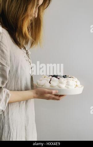 Woman tasting cake. Homemade meringue cake Pavlova with whipped cream, sugar powder, fresh blueberries and blueberry - Stock Photo