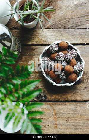 Chocolate truffles covered in nuts, on a wooden table.