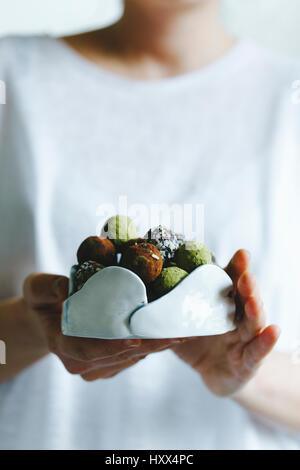 A woman holding a bowl of mixed matcha and chocolate homemade sweets - Stock Photo