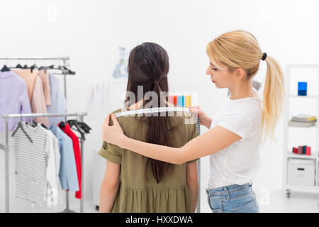 young dressmaker gets shoulders measures of client in the showroom - Stock Photo