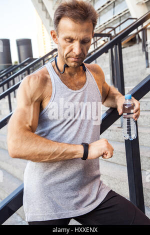 Sportsman with bottle of water is resting and checking his smart watch after running. fitness, sport, exercising - Stock Photo