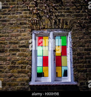 stained glass window illuminated white painted window frame in brick wall - Stock Photo