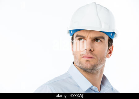 Pensive male architect in hard hat looking at distance - Stock Photo