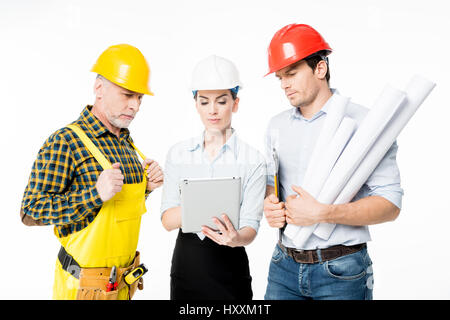 Two architects and mature workman looking at digital tablet - Stock Photo