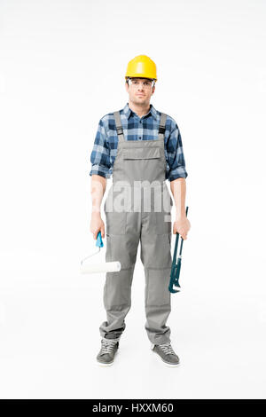 Professional male construction worker holding pipe wrench and paint roller - Stock Photo