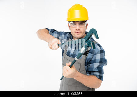 Professional male construction worker in helmet and protective eyewear holding pipe wrench - Stock Photo