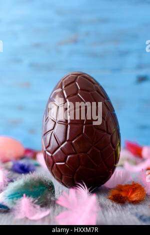 closeup of a chocolate easter egg on a rustic wooden table sprinkled with feathers of different colors, against - Stock Photo