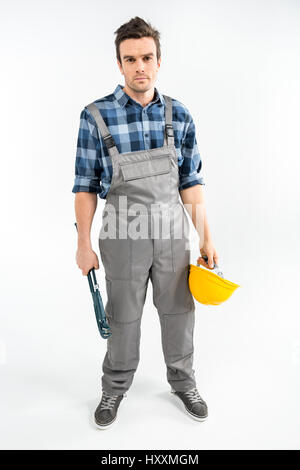 Professional male construction worker holding pipe wrench and hard hat - Stock Photo