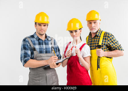 Group of professional male and female construction workers looking at camera - Stock Photo