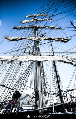 Collapsed sails on mast, big sailing yacht in harbor. - Stock Photo