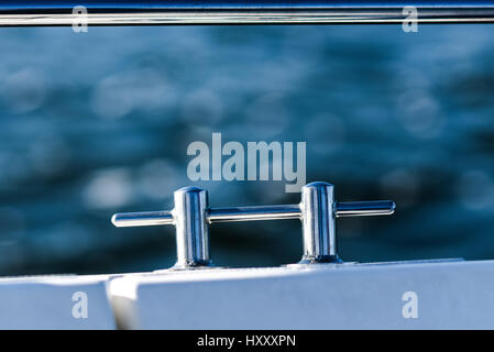 Chrome cleat on a white sailboat by the sea. - Stock Photo