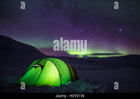 Tenting under the aurora - Stock Photo