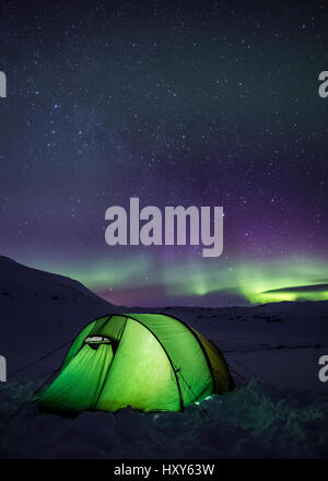 Tenting under the aurora - Stock Photo