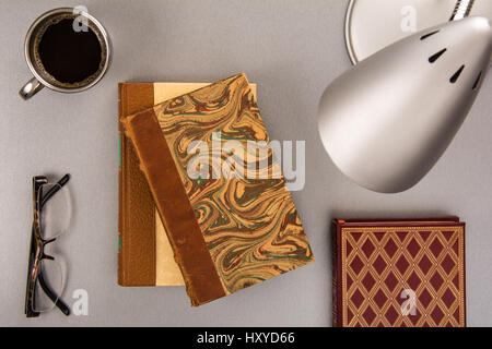 high angle view of old books on a modern desk with a cup of coffee - Stock Photo