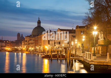 Dawn on Grand Canal in Venice, Italy. Sestiere of Santa Croce, dome of San Simeone Piccolo church in the distance. - Stock Photo