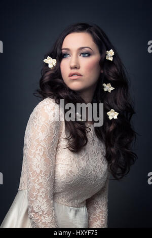 Woman wearing white lace dress, looking away - Stock Photo