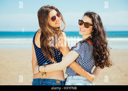 Happy girl friends hugging on the beach - Stock Photo