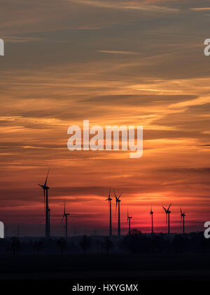 Wind power plants at sundown with colorful clouds and sky - Stock Photo