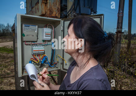 Woman Technician reading the electricity meter to check consumption, standing near electricity switchgear  power - Stock Photo