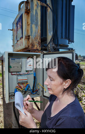 Woman electrician engineer inspecting electric counter equipment in distribution fuse box, electricity switchgear - Stock Photo