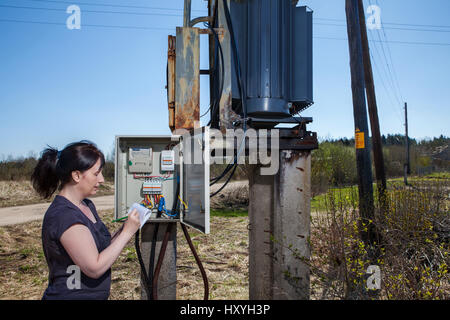 Electrician engineer  woman checking electricity meter and invoice,  standing near electricity switchgear  power - Stock Photo