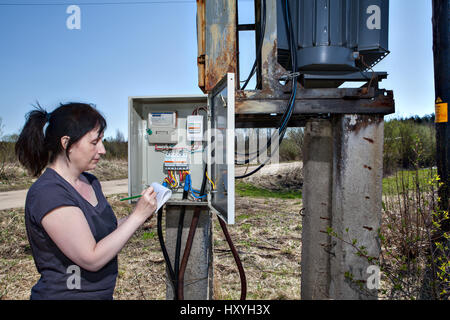 Technician woman checking electricity meter and invoice,  standing near electricity switchgear  power transformer - Stock Photo