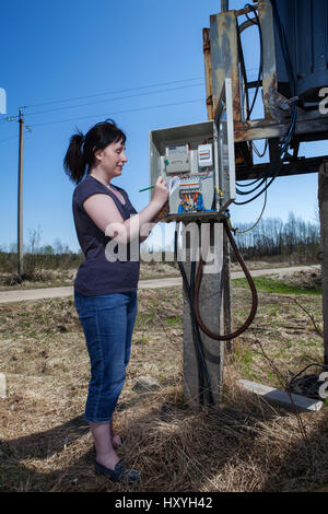 Woman checking electric meter reading, standing near electricity switchgear  power transformer substation, outdoors. - Stock Photo