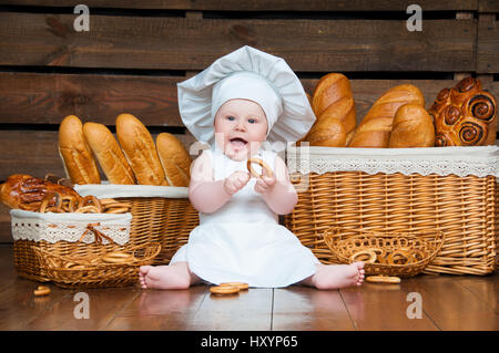 Child cooks eating a bagel on the background of baskets with rolls and bread. - Stock Photo