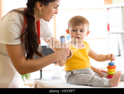 doctor measuring temperature cute kid - Stock Photo