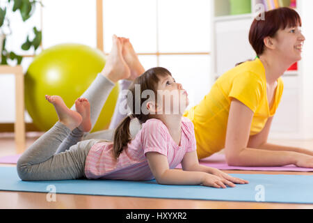 Mother and daughter doing gymnastics exercises on mat at home. - Stock Photo