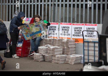 Evening Standard newspaper street vendor selling the long-established London evening newspaper outside Waterloo - Stock Photo