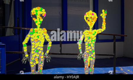 People pass by two alien figures in front of the International UFO Museum and Research Center in Roswell, New Mexico - Stock Photo