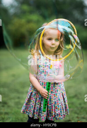 Young Bond Girl Blowing a Giant Soap Bubble in the Park - Stock Photo