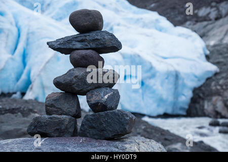 A cairn built on a rock in the recessional moraine of the bear glacier looks like a small person. The stack of dark - Stock Photo