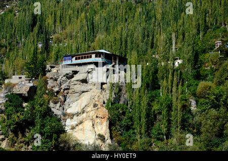 A building stands on top of a rocky ledge in Hunza Valley Pakistan - Stock Photo