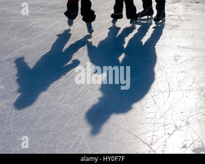 Silhouettes and shadows of three ice skaters on ice rink. - Stock Photo