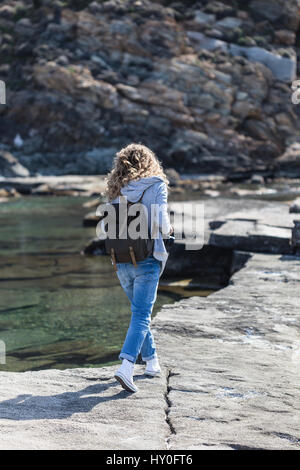 Full length portrait of blond woman tourist with khaki backpack wearing jeans and gray jacket walking on rock ribbed - Stock Photo