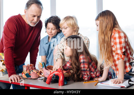 Your bodys engine. Dedicated intelligent pleasant man delivering a lecture on heart functions and ways of work while - Stock Photo